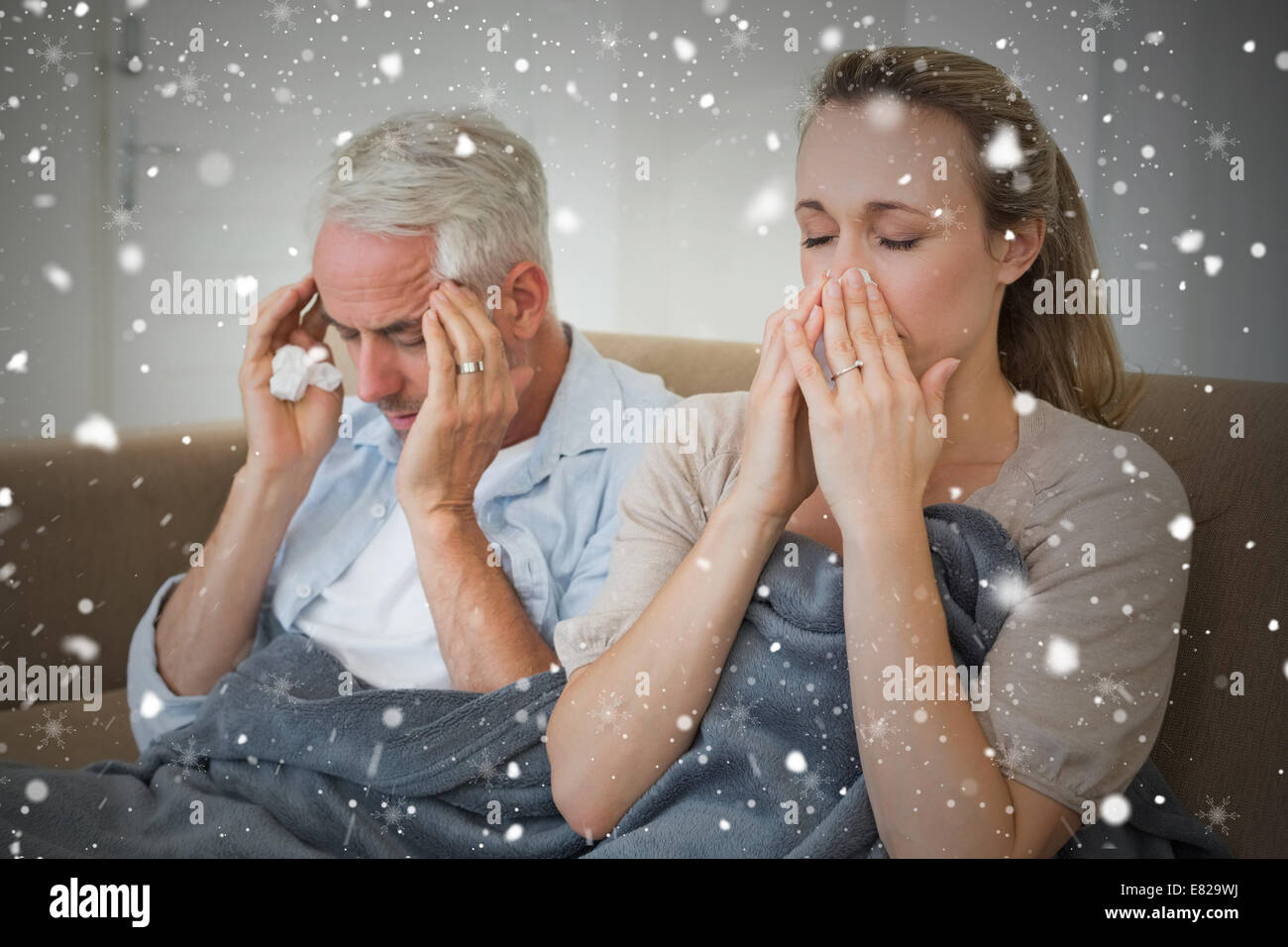 Composite image of sick couple sitting on the couch under a blanket - Stock Image