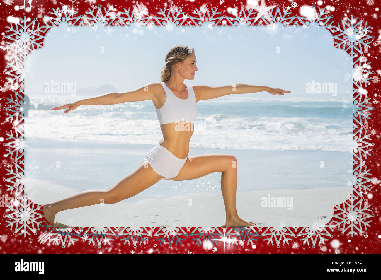 Gorgeous blonde in warrior pose by the sea - Stock Image
