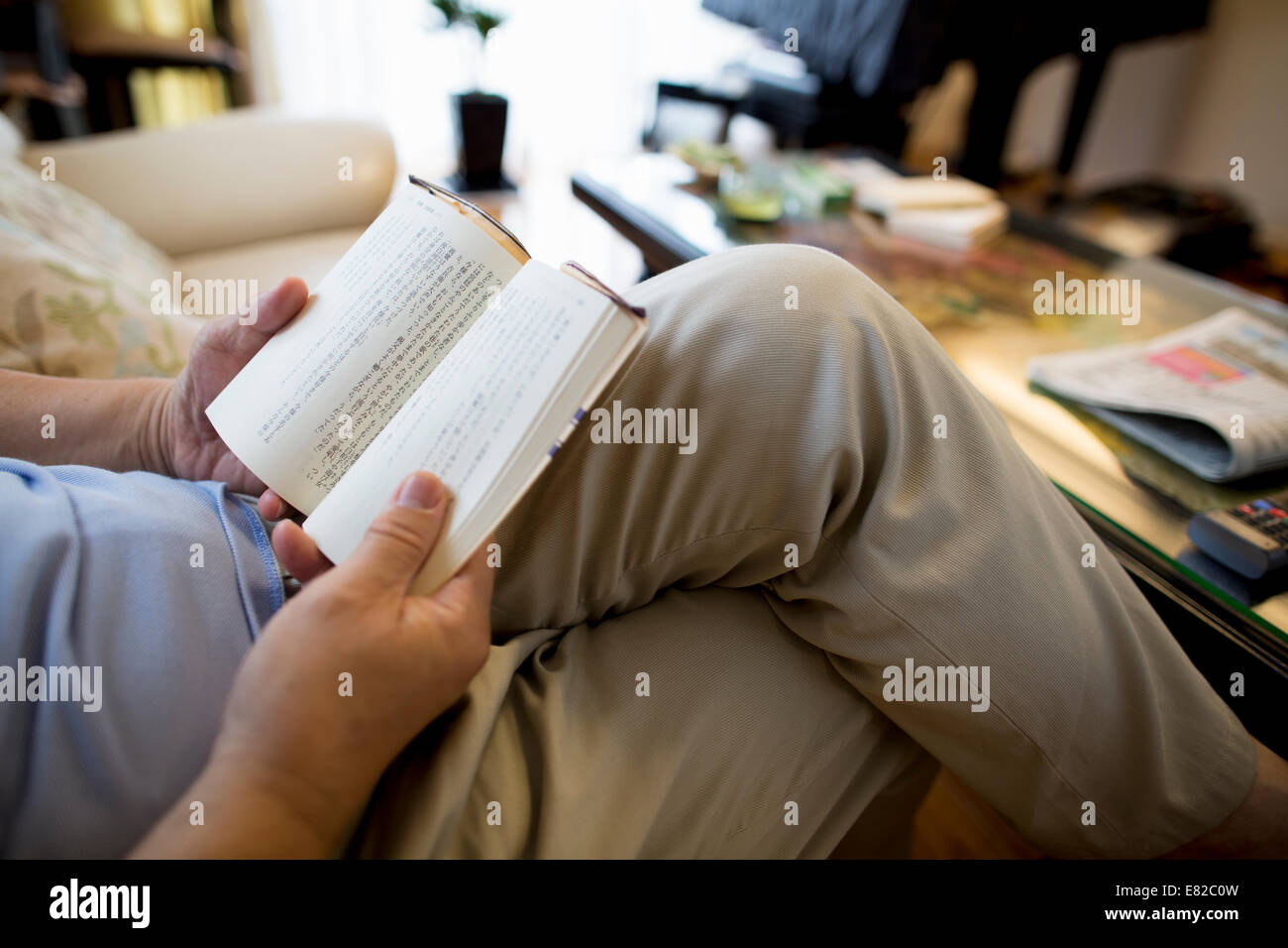 Man sitting on sofa reading a book. - Stock Image