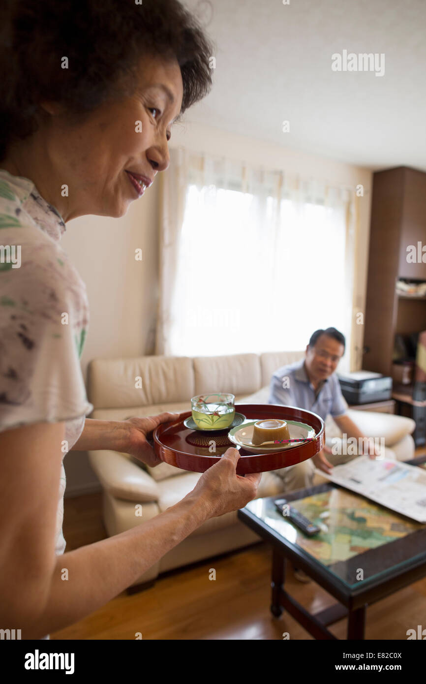 A woman serving a tray of food to a man sitting on a sofa. - Stock Image