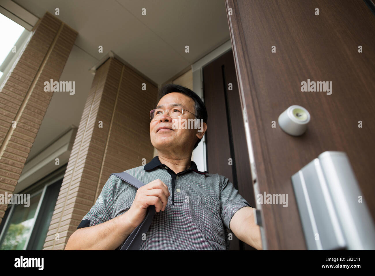 A man standing at his front door. - Stock Image