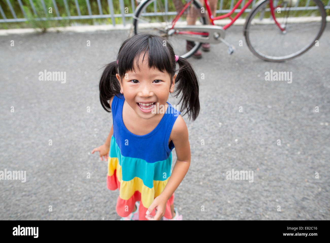 A young girl with pigtails smiling at the camera. Stock Photo