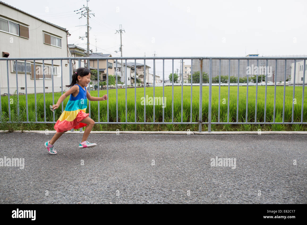 A young girl running along a footpath. - Stock Image