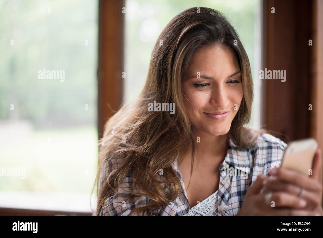 A woman sitting by a window, looking at her cell phone. - Stock Image