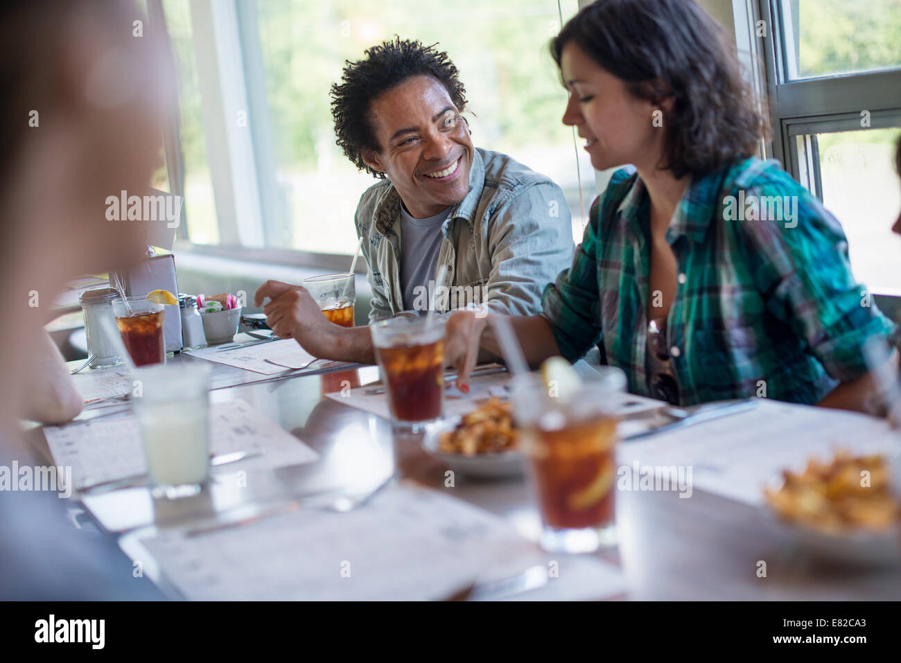 A group of friends eating at a diner. A couple seated side by side. - Stock Image