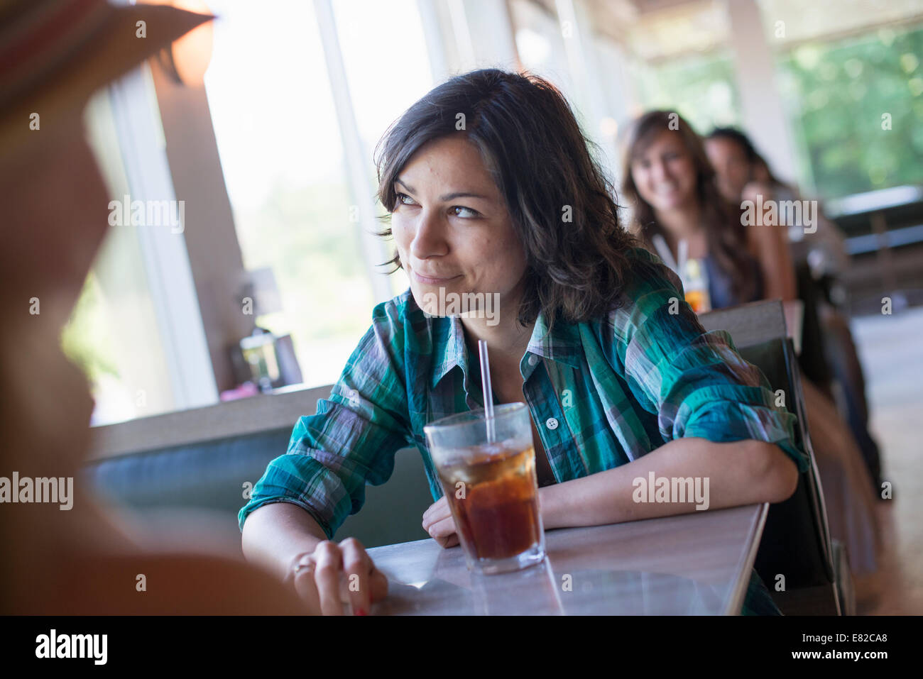 A woman seated at a diner looking out of the window. A long cool drink with a straw. - Stock Image