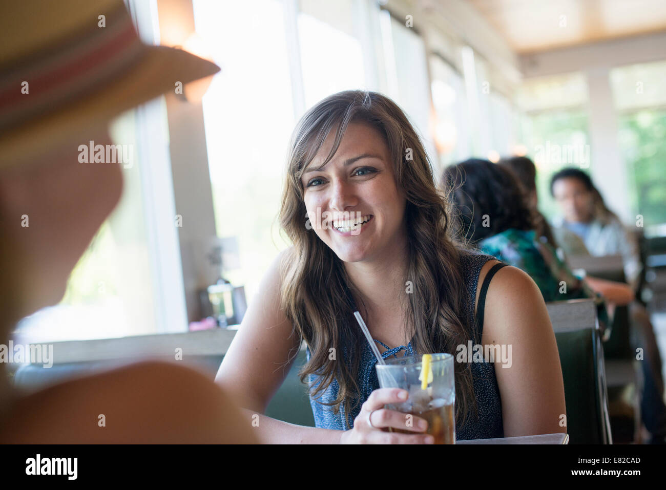 A woman sitting at a diner table holding a cool drink. - Stock Image