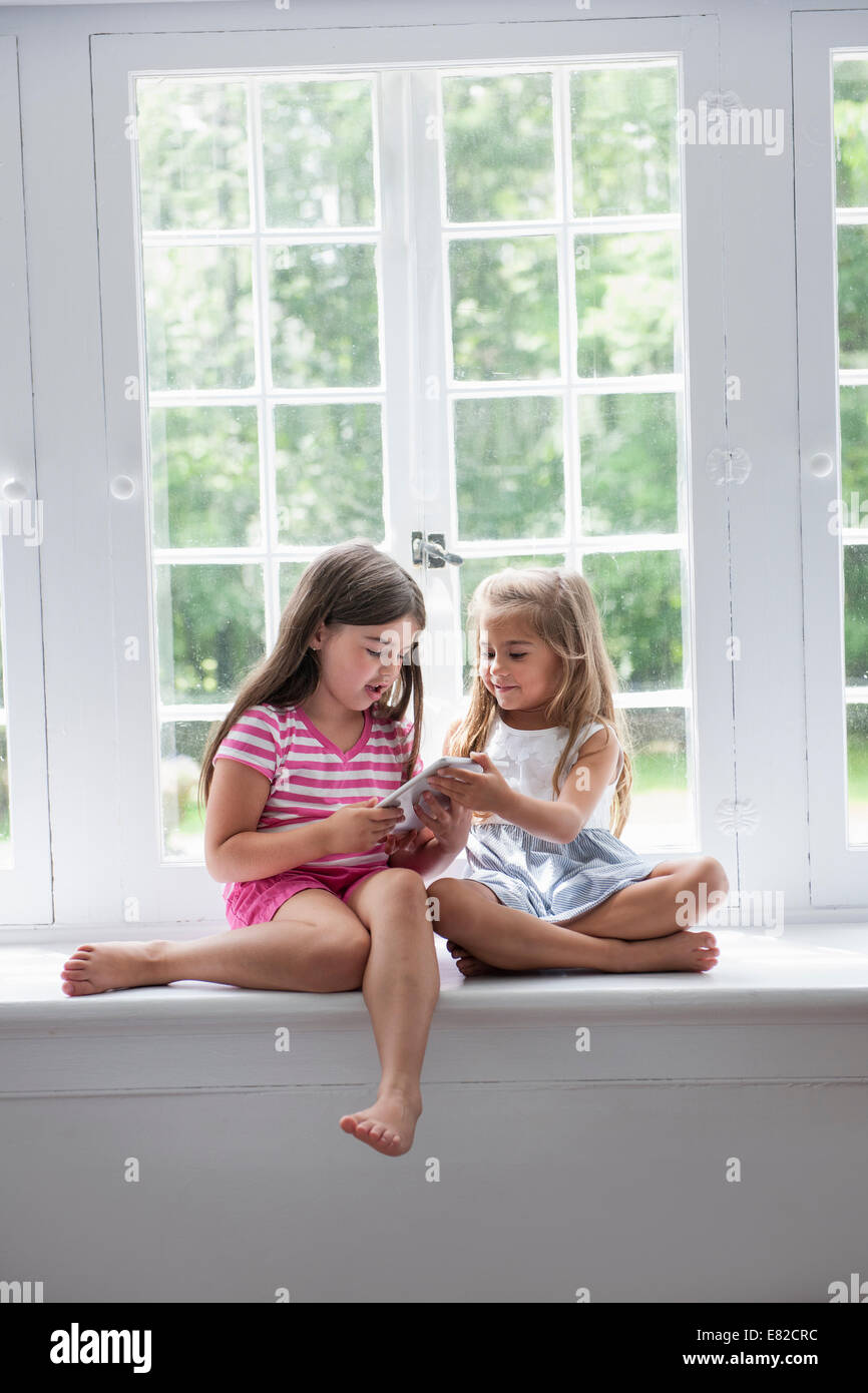 Two girls playing, sharing a digital tablet. - Stock Image