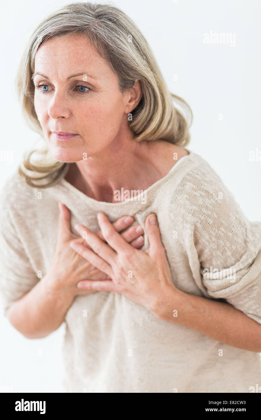 Woman suffering from a mild heart attack. - Stock Image