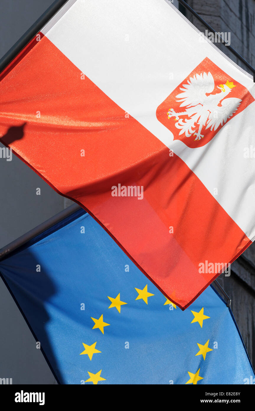 Estonia, Tallinn. The Polish and European Union flags overlap as they fly from flagpoles over a shop in Tallinn. - Stock Image