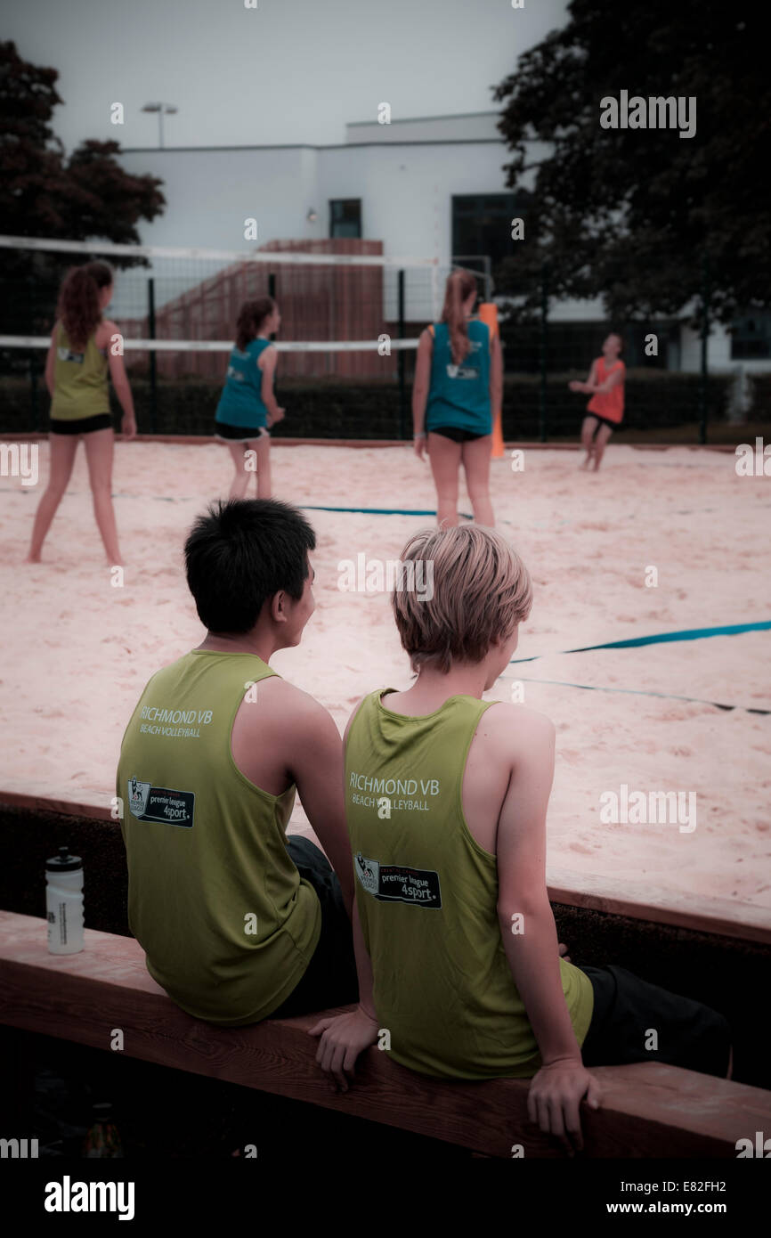 Two young people wait on the bench for their turn to play on a park volleyball court. - Stock Image