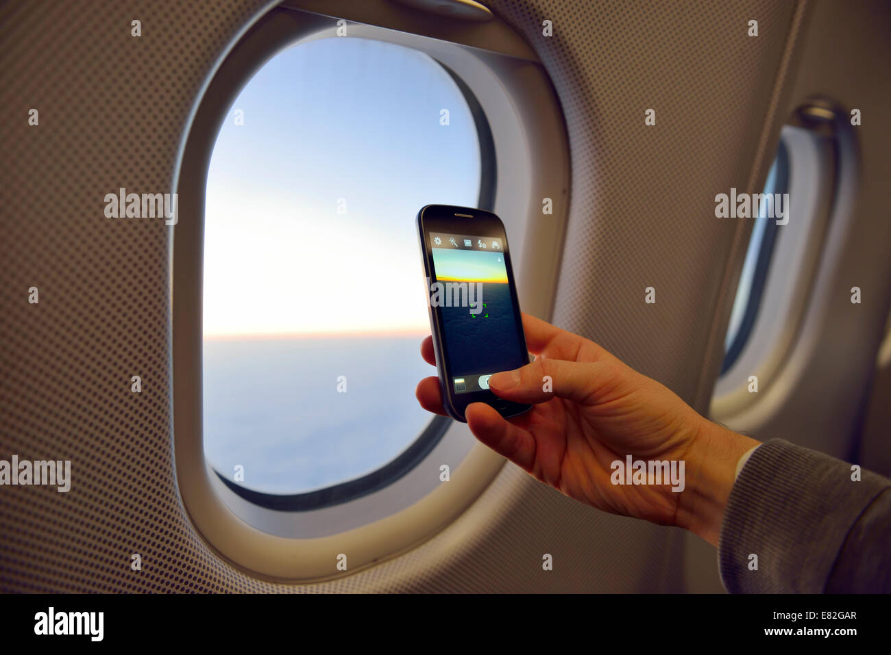 Man taking picture with smartphone at airplane window - Stock Image