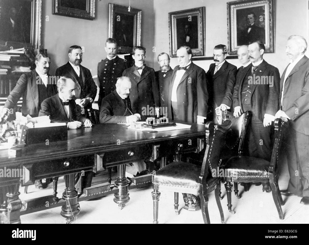 French Ambassador Pierre Paul Cambon signing the Peace Protocol, as President William McKinley and ten other men - Stock Image