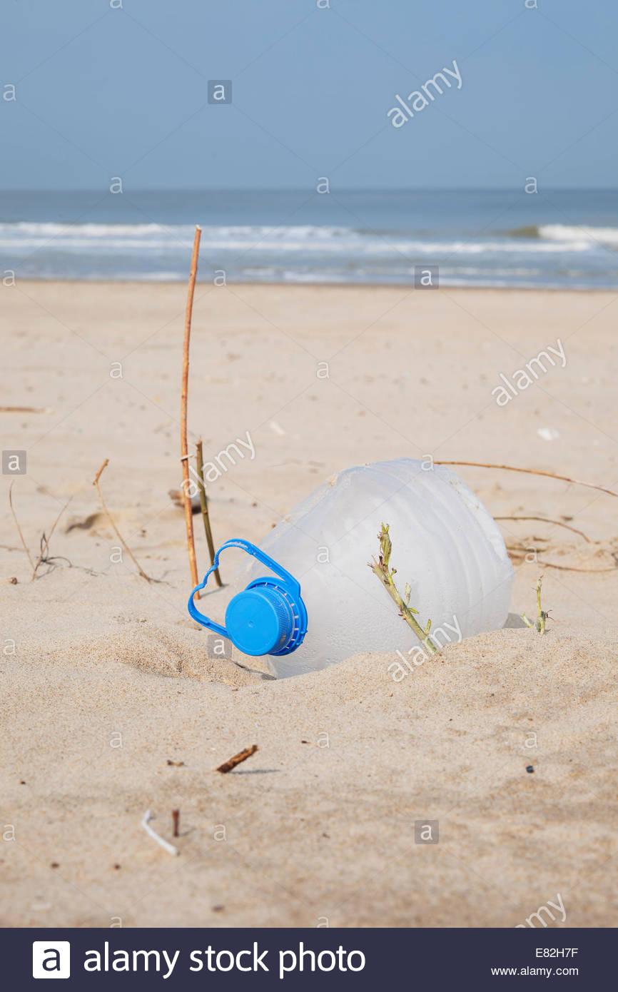 Belgium, empty plastic bottle lying on sandy beach at North Sea coast - Stock Image