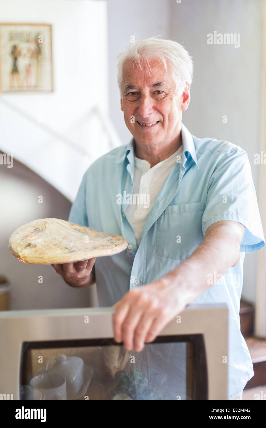 Man using a microwave oven. - Stock Image