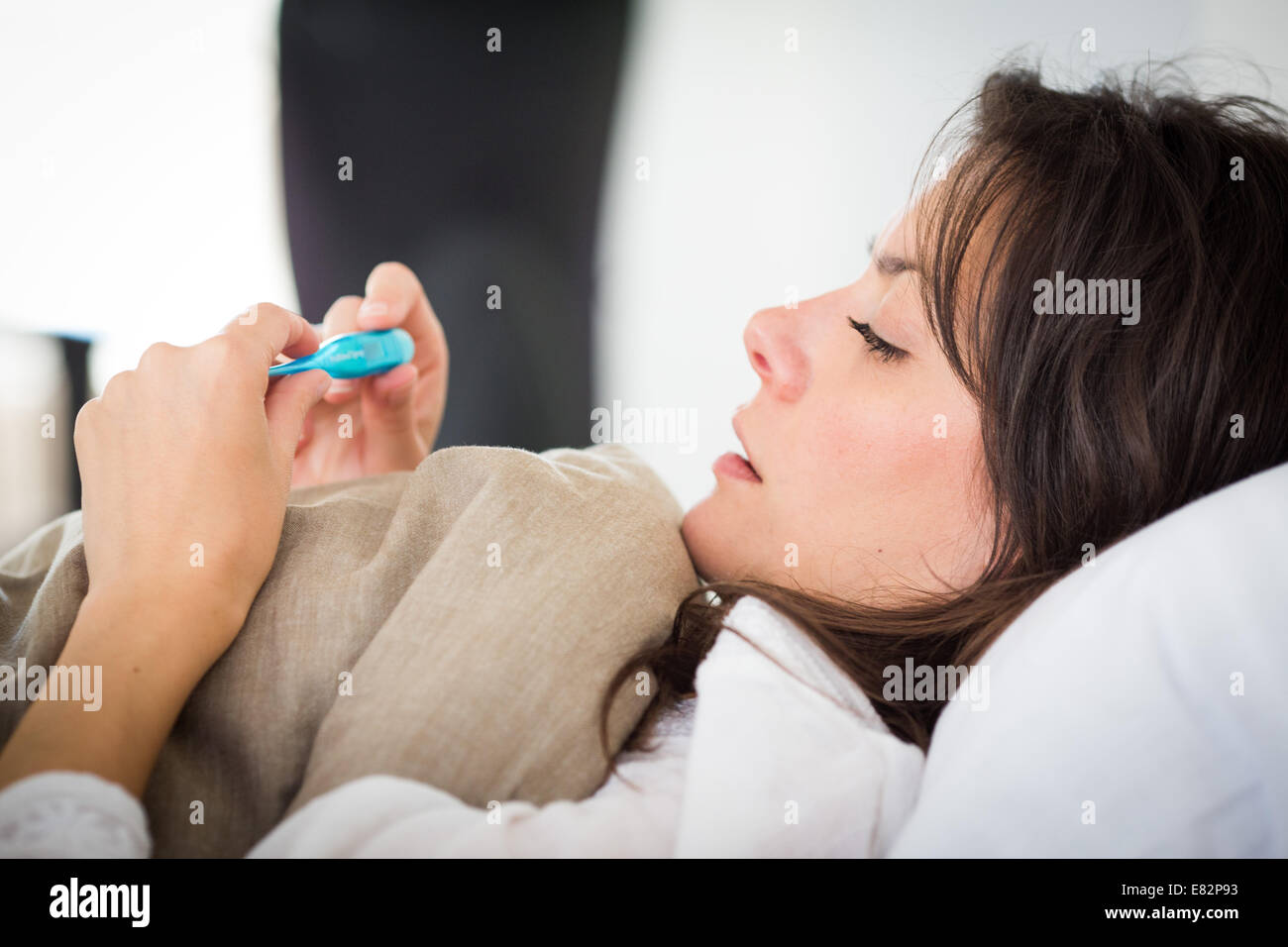 Woman checking her temperature with a digital thermometer. - Stock Image