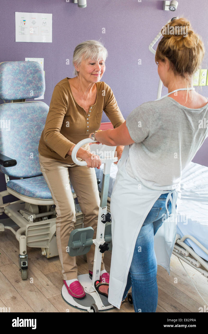 Ergonomic Equipment Disabled Room, Here, woman using a handlebar transfer facilitating the passage sit / stand. - Stock Image