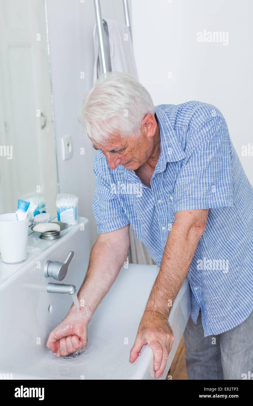 Man's hand under running water. - Stock Image