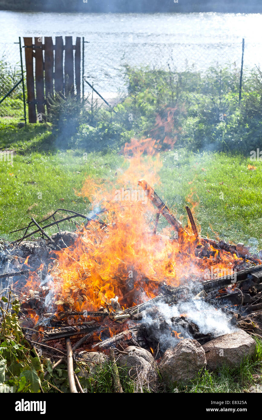 Garbage in fire, illegal garden burning out. - Stock Image