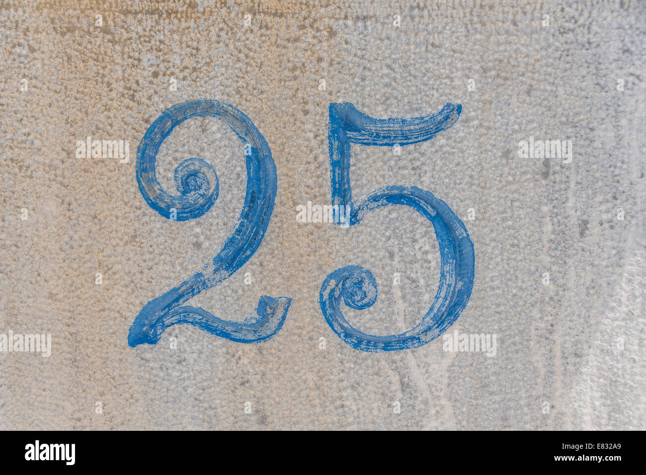 Number 25 painted on stone in an ornate blue font - Stock Image