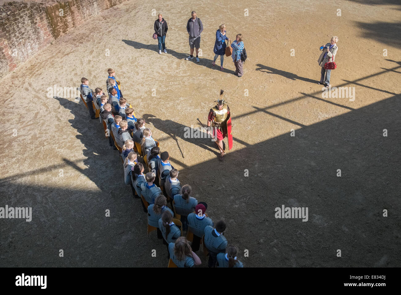 Primary school children having a roman history lesson at the Roman Ampitheatre, Chester, Cheshire, England UK - Stock Image
