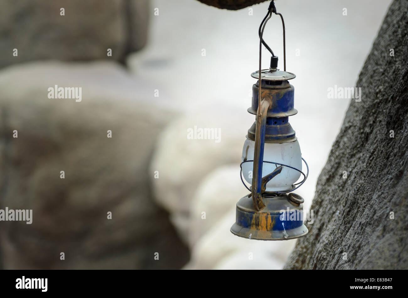 Old vintage oil lamp hangs in a dark cavern - Stock Image