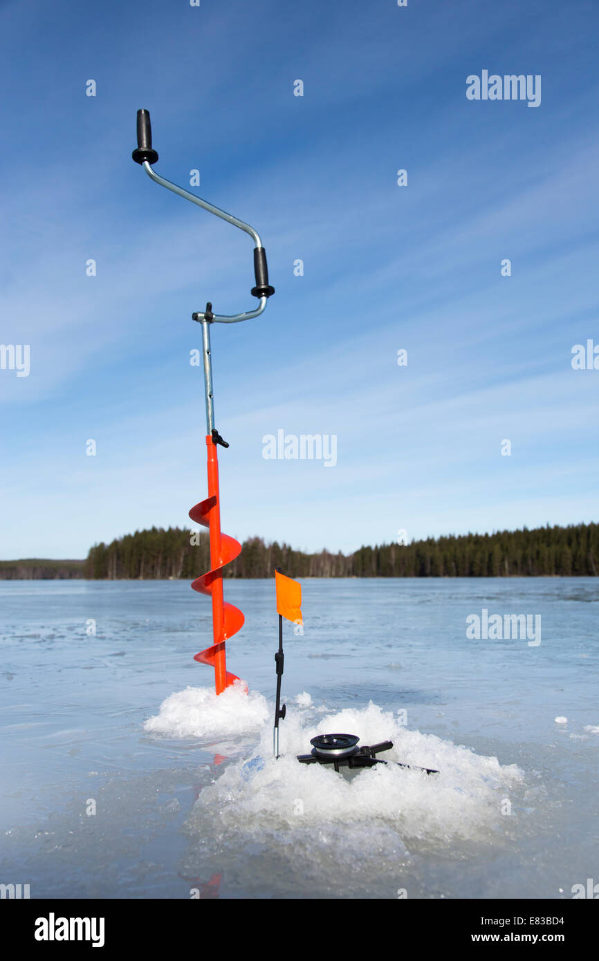 Hand ice auger and tip-up ice fishing rod , Finland Stock Photo