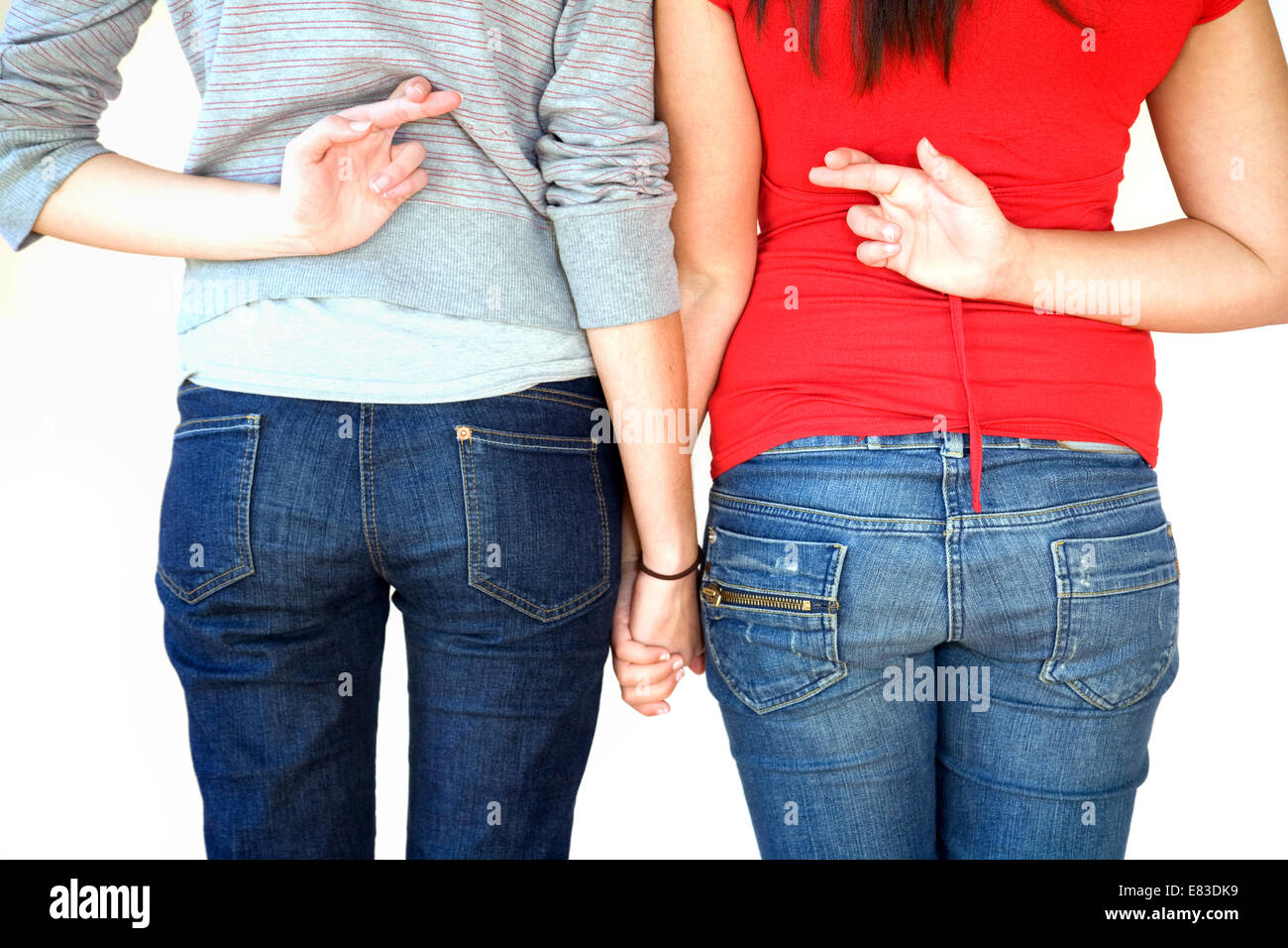 Two teenage girls standing holding hands with fingers crossed behind their backs; UK - Stock Image
