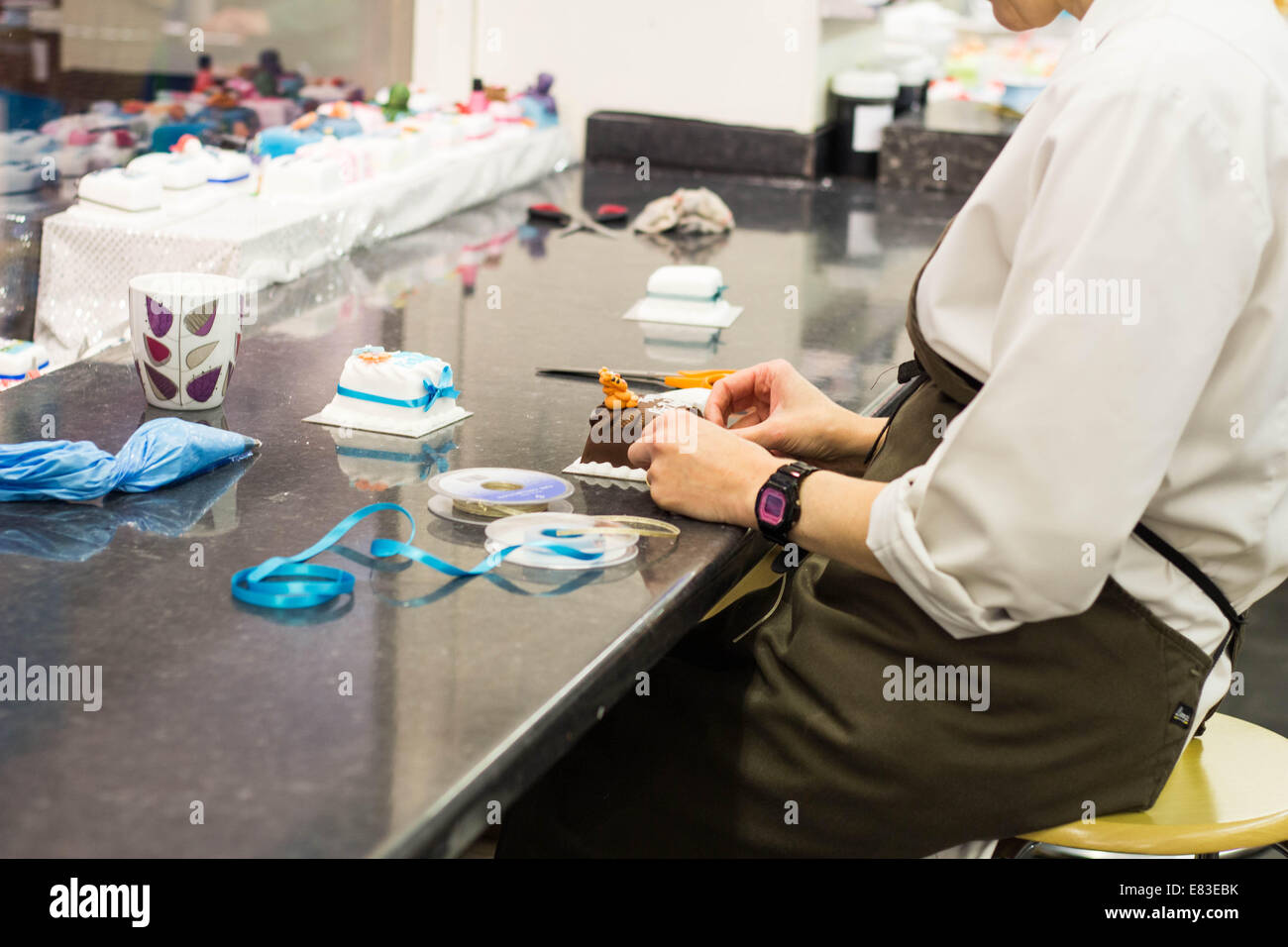 Woman decorating cakes. - Stock Image