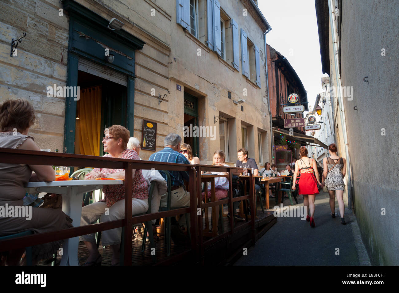 Small eating area outside restaurant in narrow French alley. - Stock Image