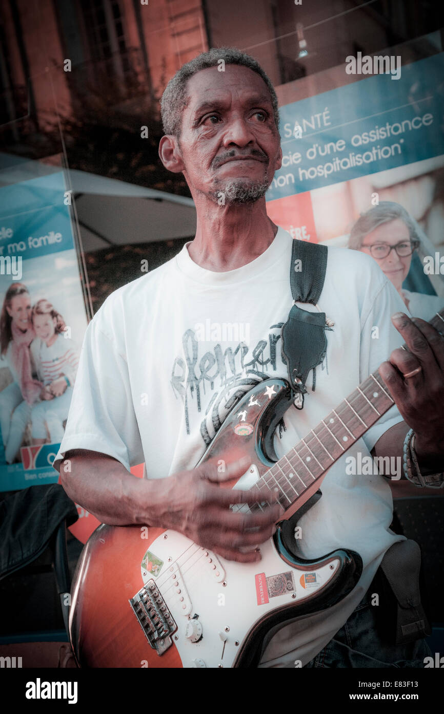 North african man playing electric guitar on the streets of Bergerac during music festival. - Stock Image