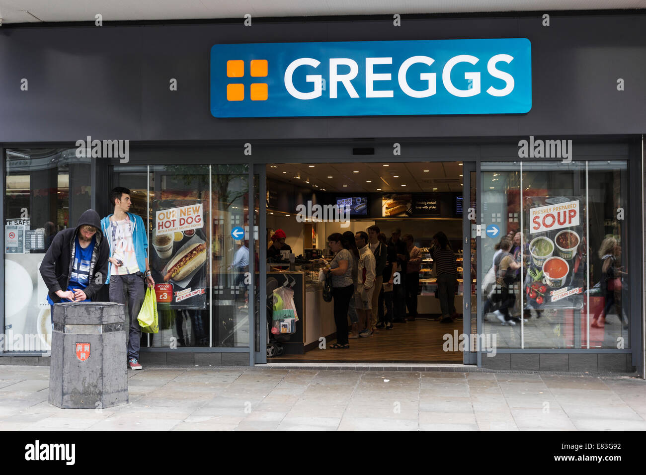 Greggs fast food outlet on Northumberland Street, Newcastle upon Tyne with customers buy food while a man searches - Stock Image