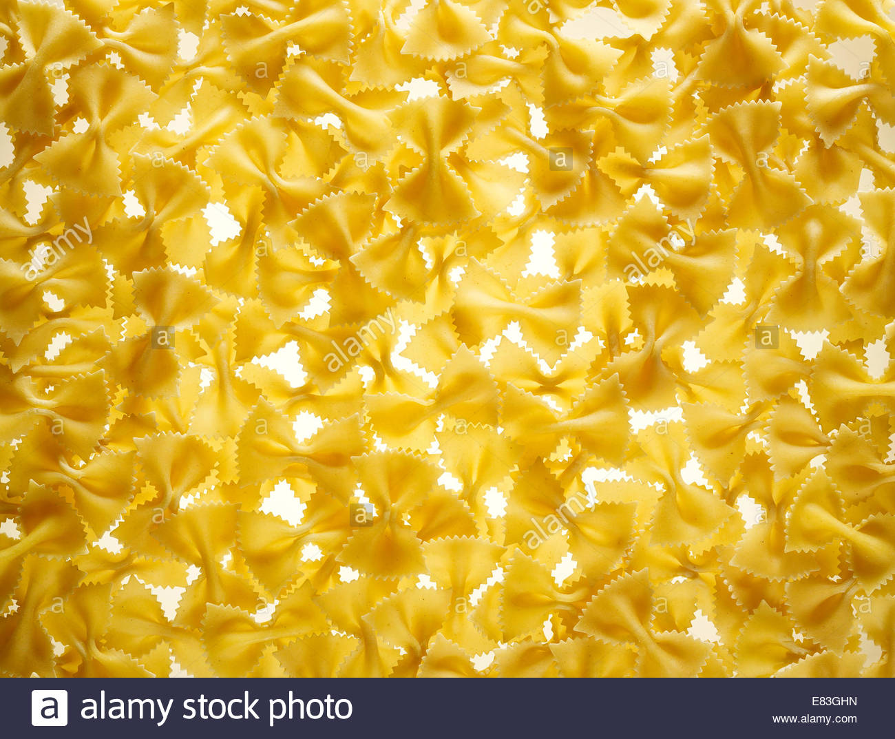 Background image of traditional Italian uncooked Bowtie Pasta - Stock Image