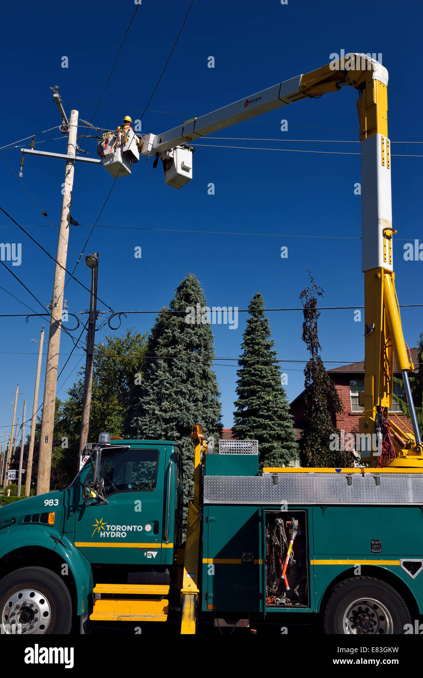 Hydro worker lineman stringing new overhead electric power lines in suburban Toronto against blue sky - Stock Image