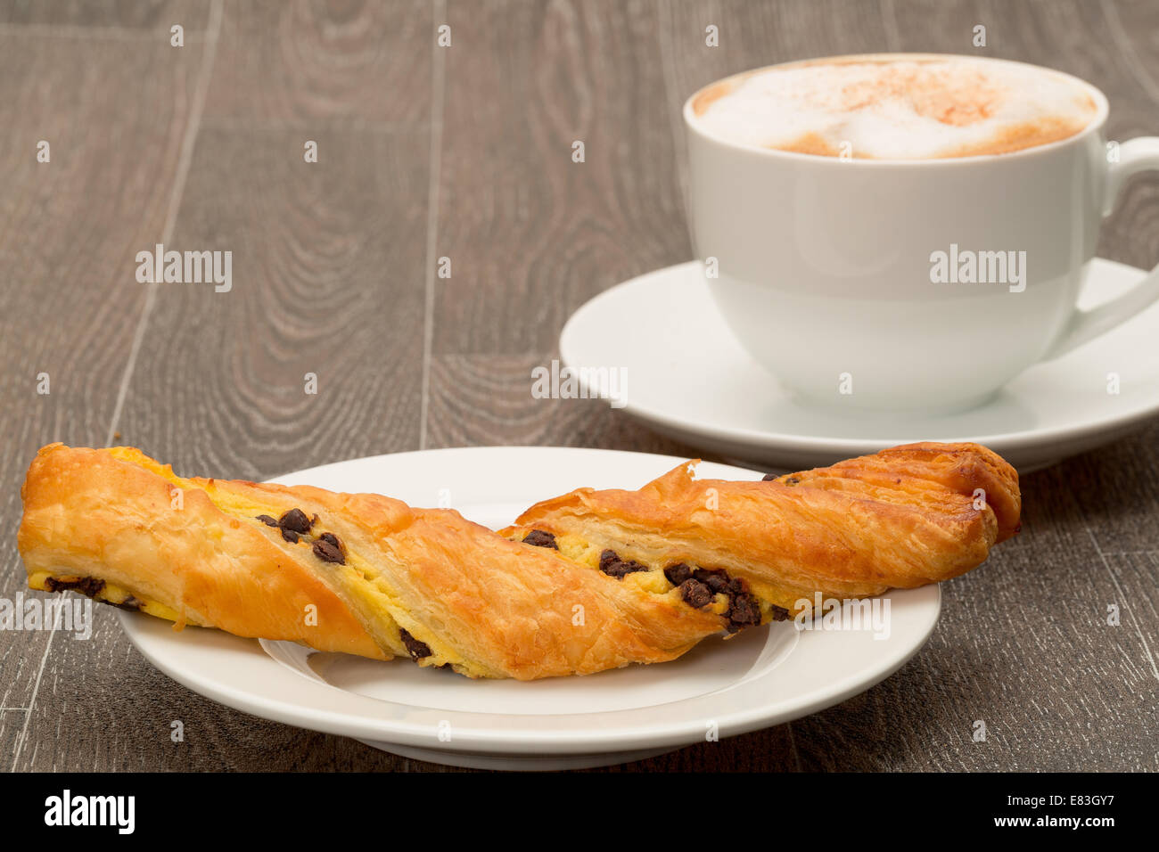 Authentic French chocolate twist pastry with a cappuccino coffee - studio shot and a shallow depth of field - Stock Image