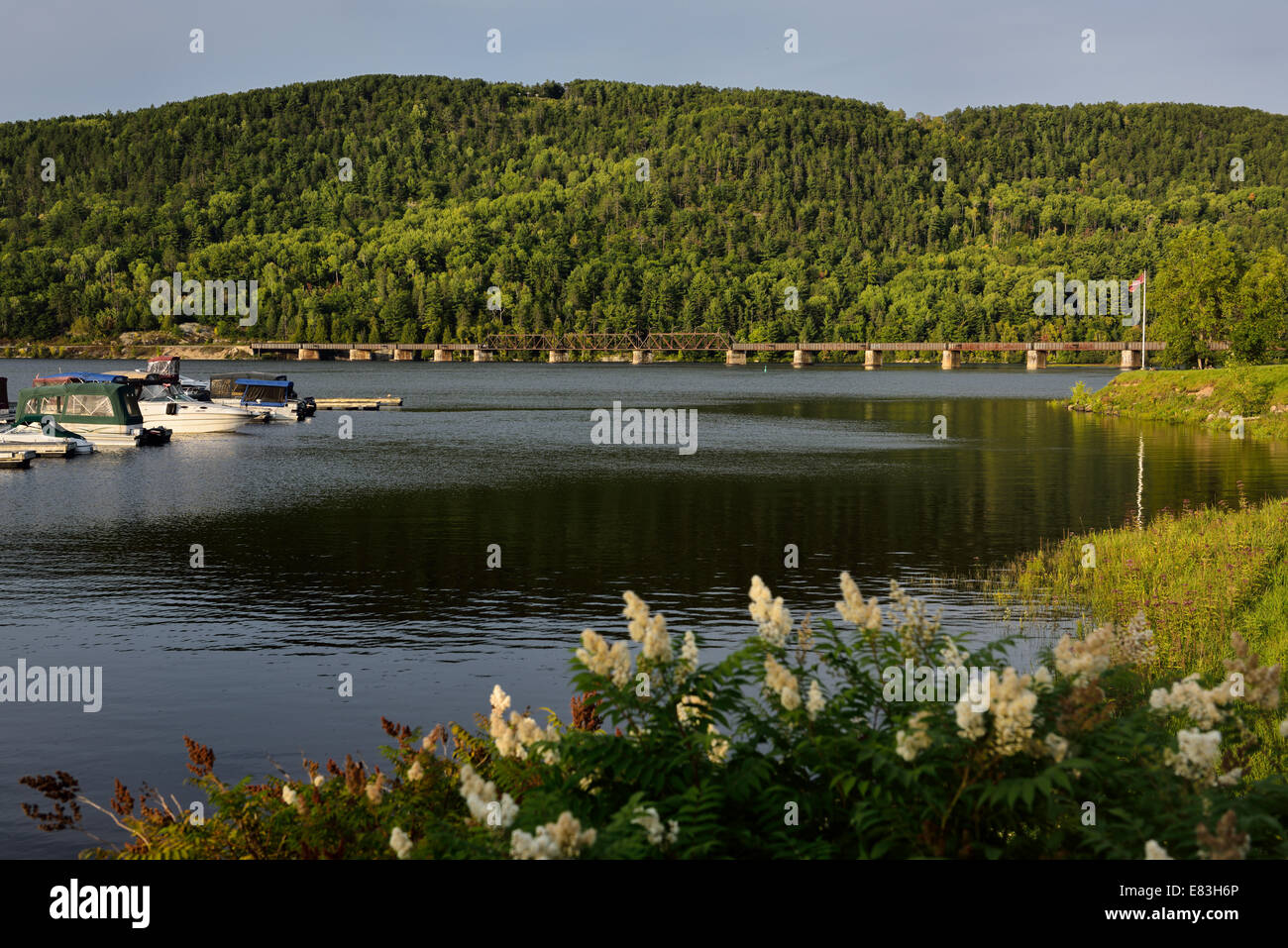 Train bridge over the Ottawa river to Quebec at Mattawa Explorers Point Park marina Ontario Canada - Stock Image