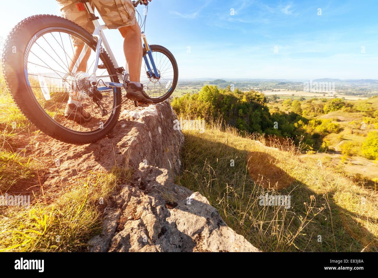 Mountain biker looking at downhill dirt track - Stock Image