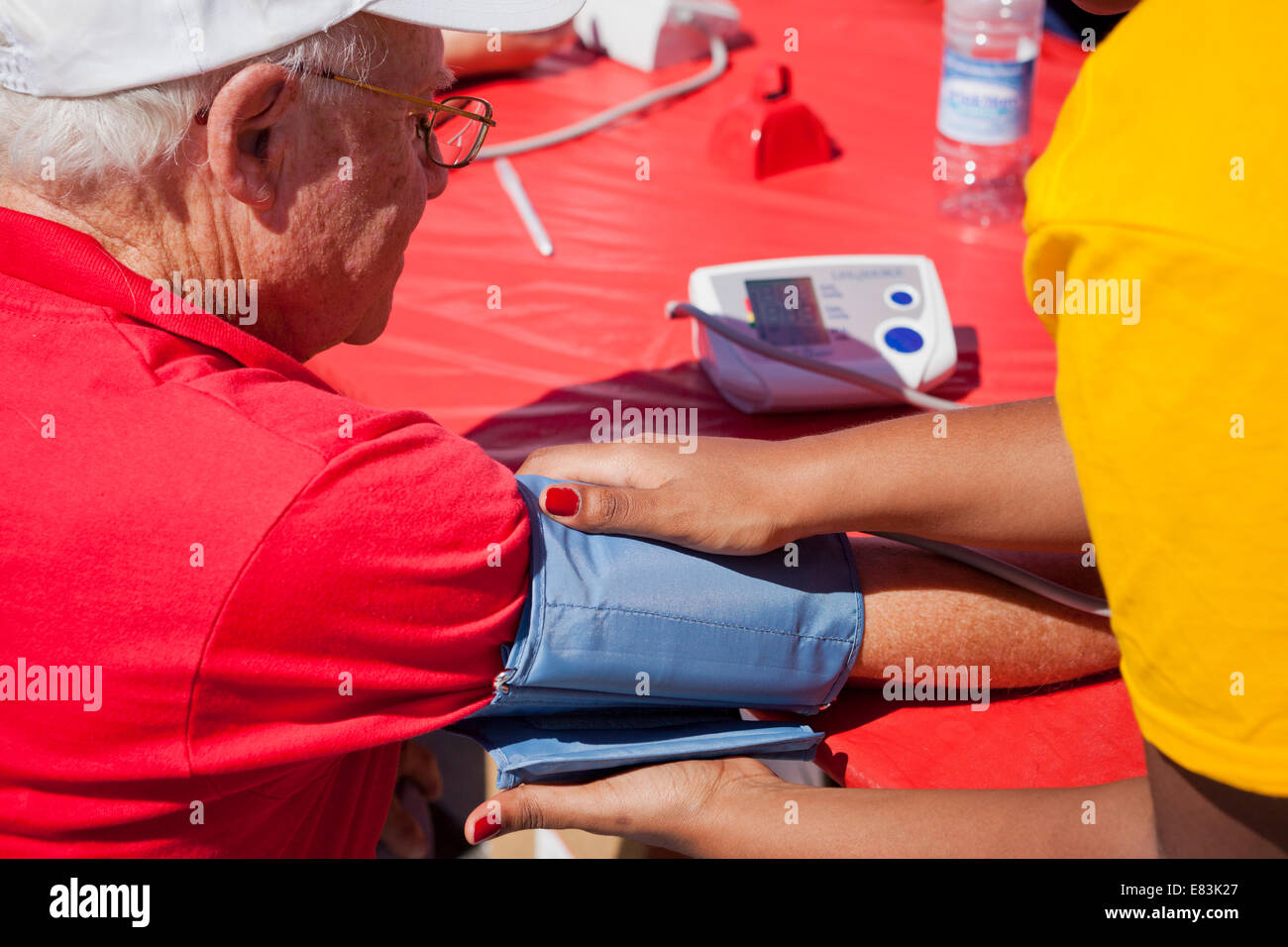 Elderly man getting blood pressure check at health fair - USA - Stock Image