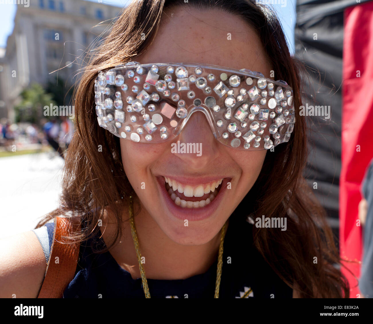 Young woman wearing funny oversize novelty sunglasses - USA - Stock Image