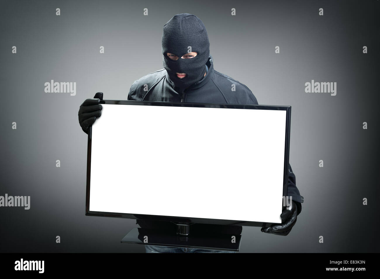Thief stealing computer monitor - Stock Image