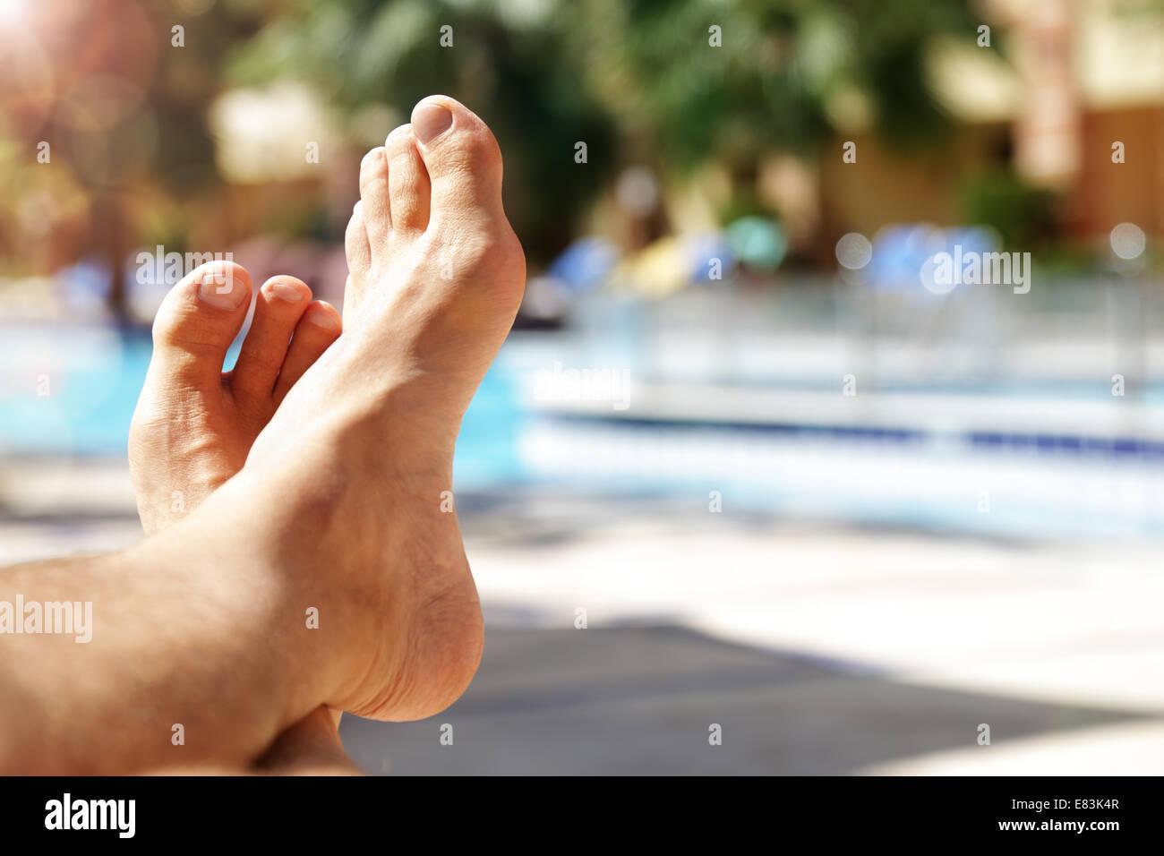 Sunbathing by swimming pool - Stock Image