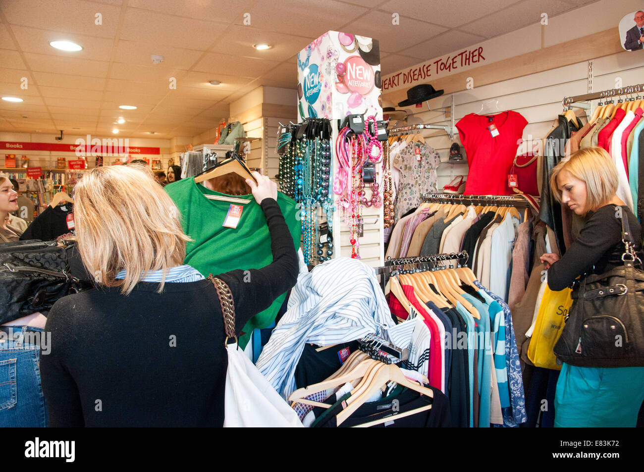 People shopping in Oxfam charity shop, London, England, UK - Stock Image