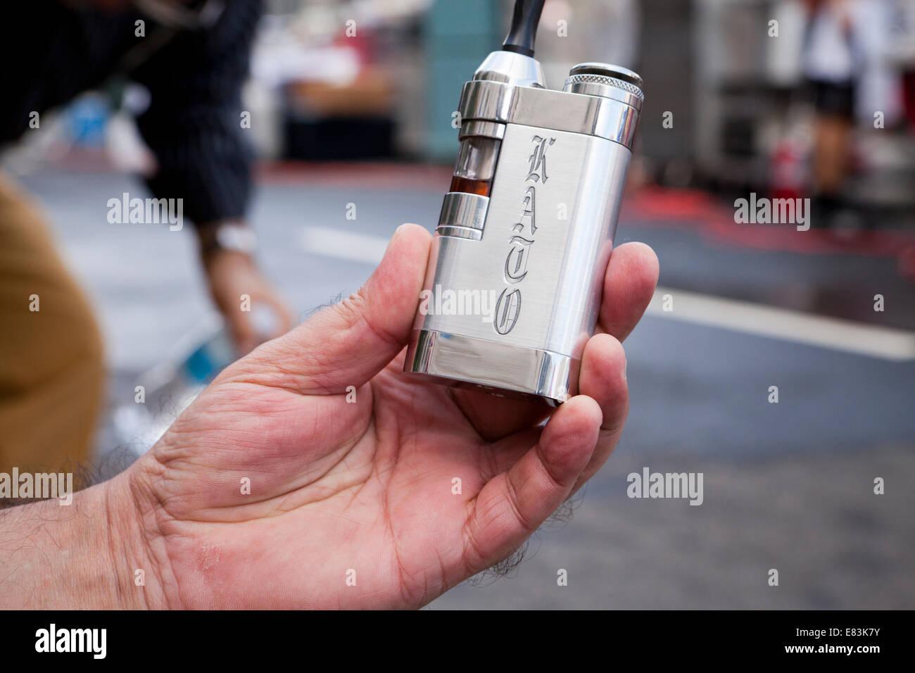 Man holding portable nicotine vaporizer - USA - Stock Image