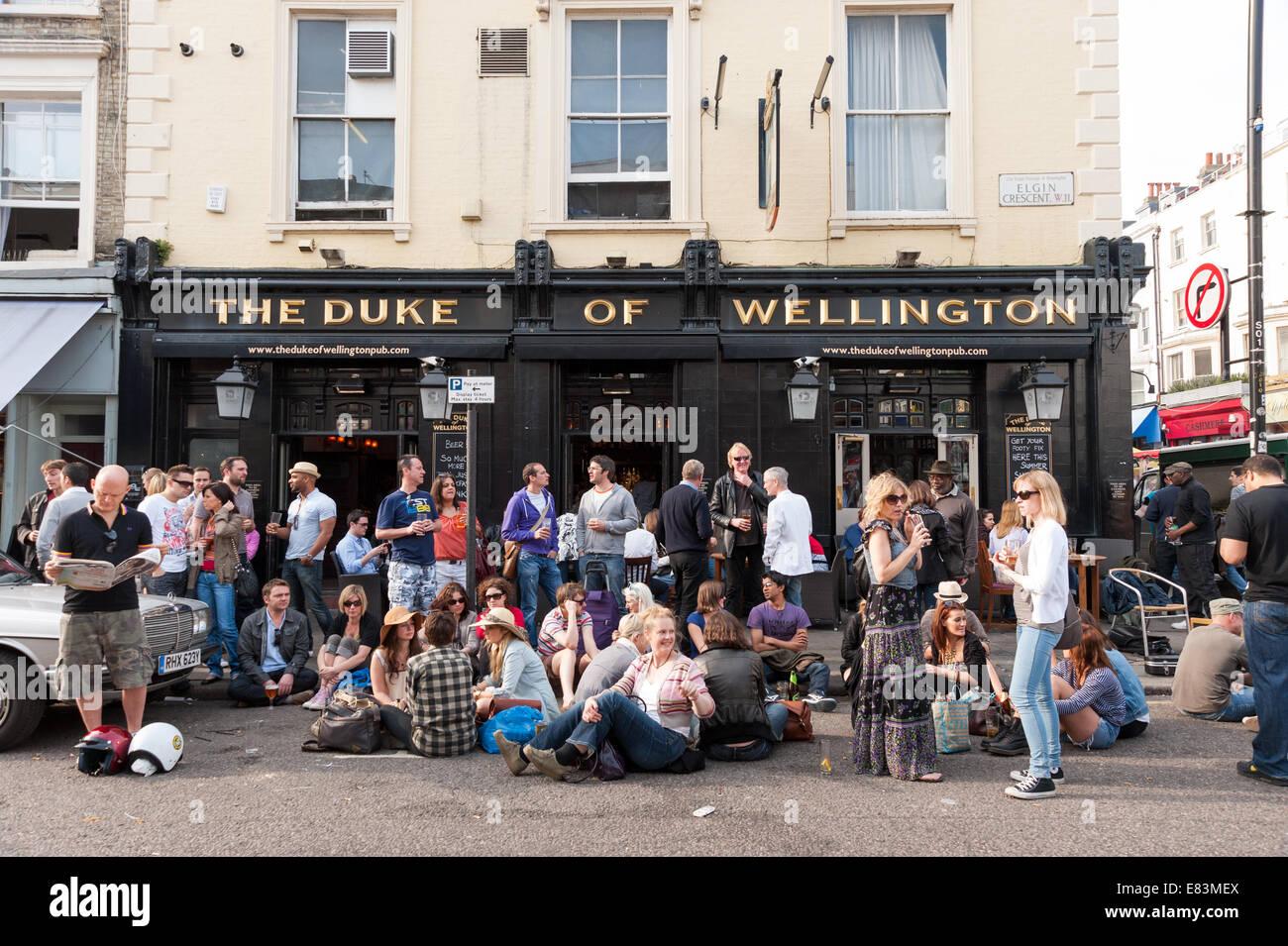 People drinking outside the Duke of Wellington pub on Portobello Road, Notting Hill, London, England, UK - Stock Image