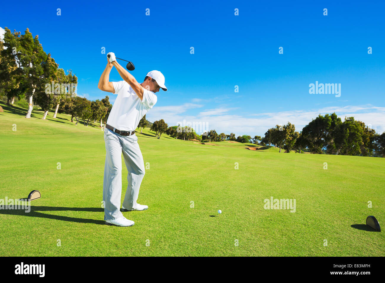 Golf player teeing off. Man hitting golf ball from tee box with driver. - Stock Image