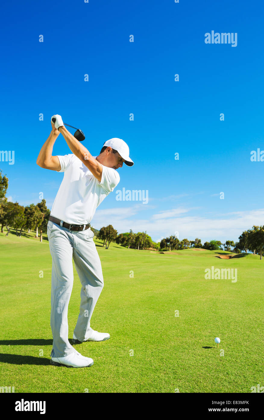 Golfer Hitting Golf Shot with Club on the Course - Stock Image