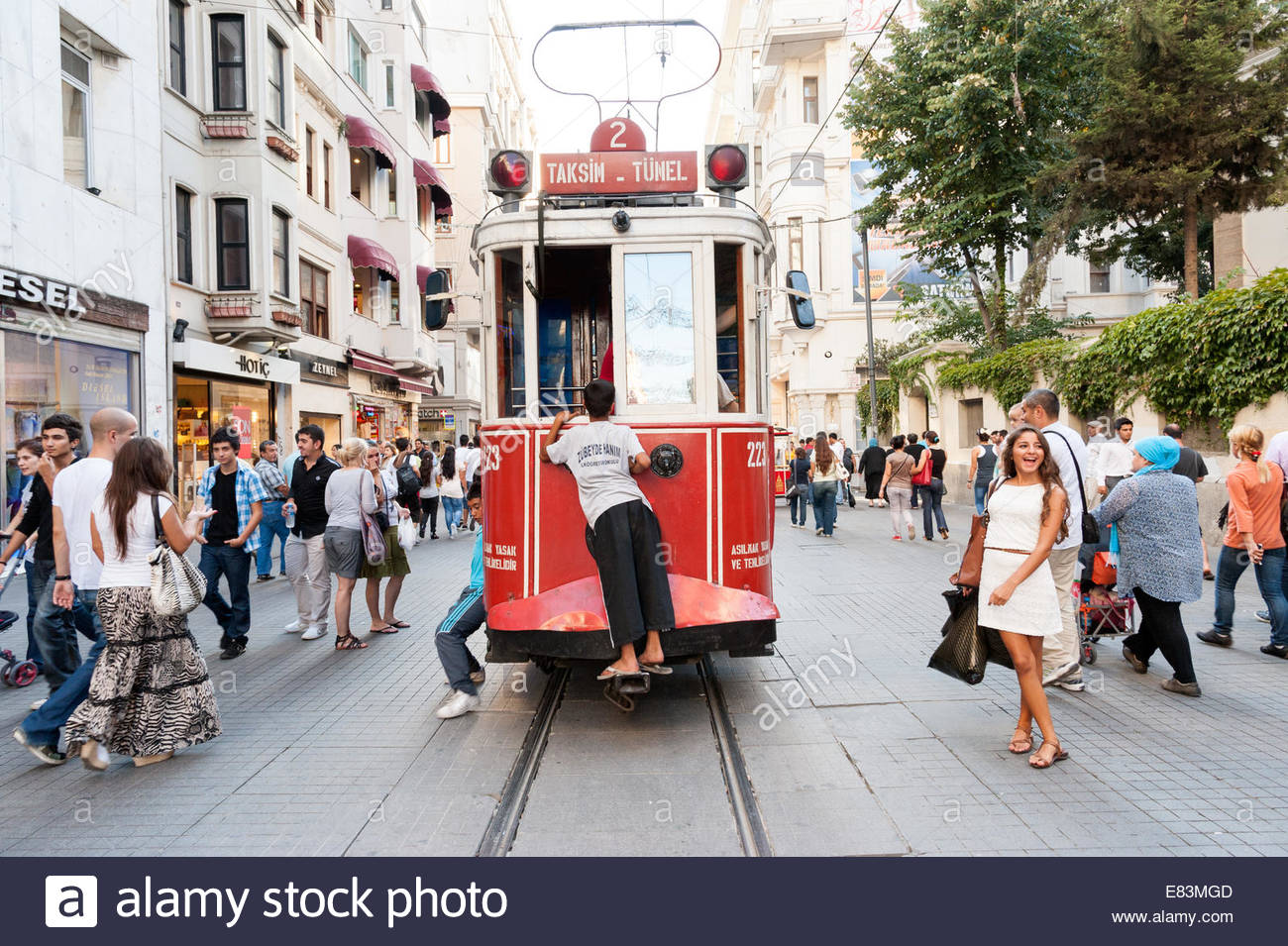 Child hitching a ride on back of an old red tram on Istiklal Cadessi, Beyoglu, Istanbul, Turkey - Stock Image