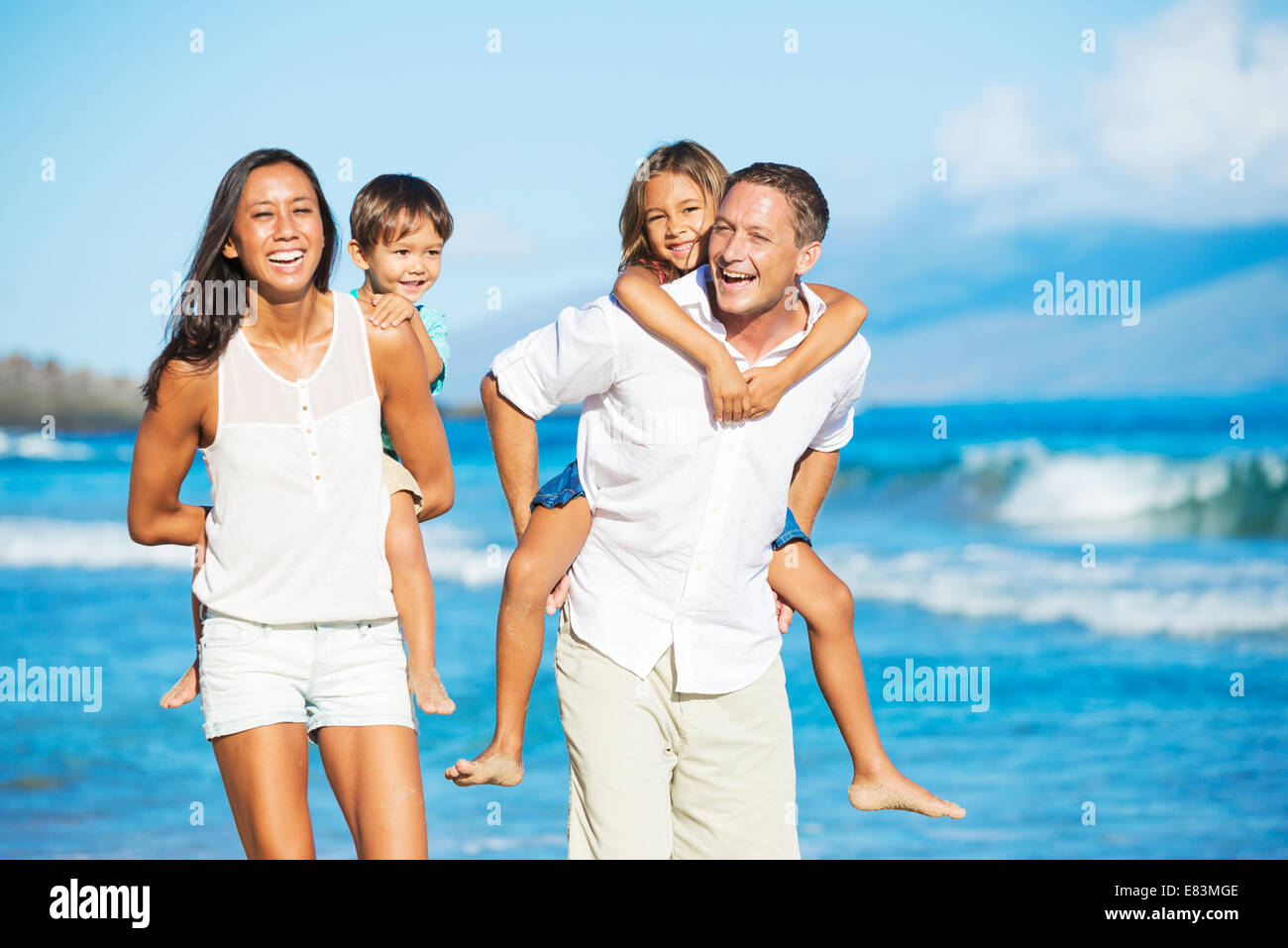 Happy Mixed Race Family of Four on the Beach - Stock Image