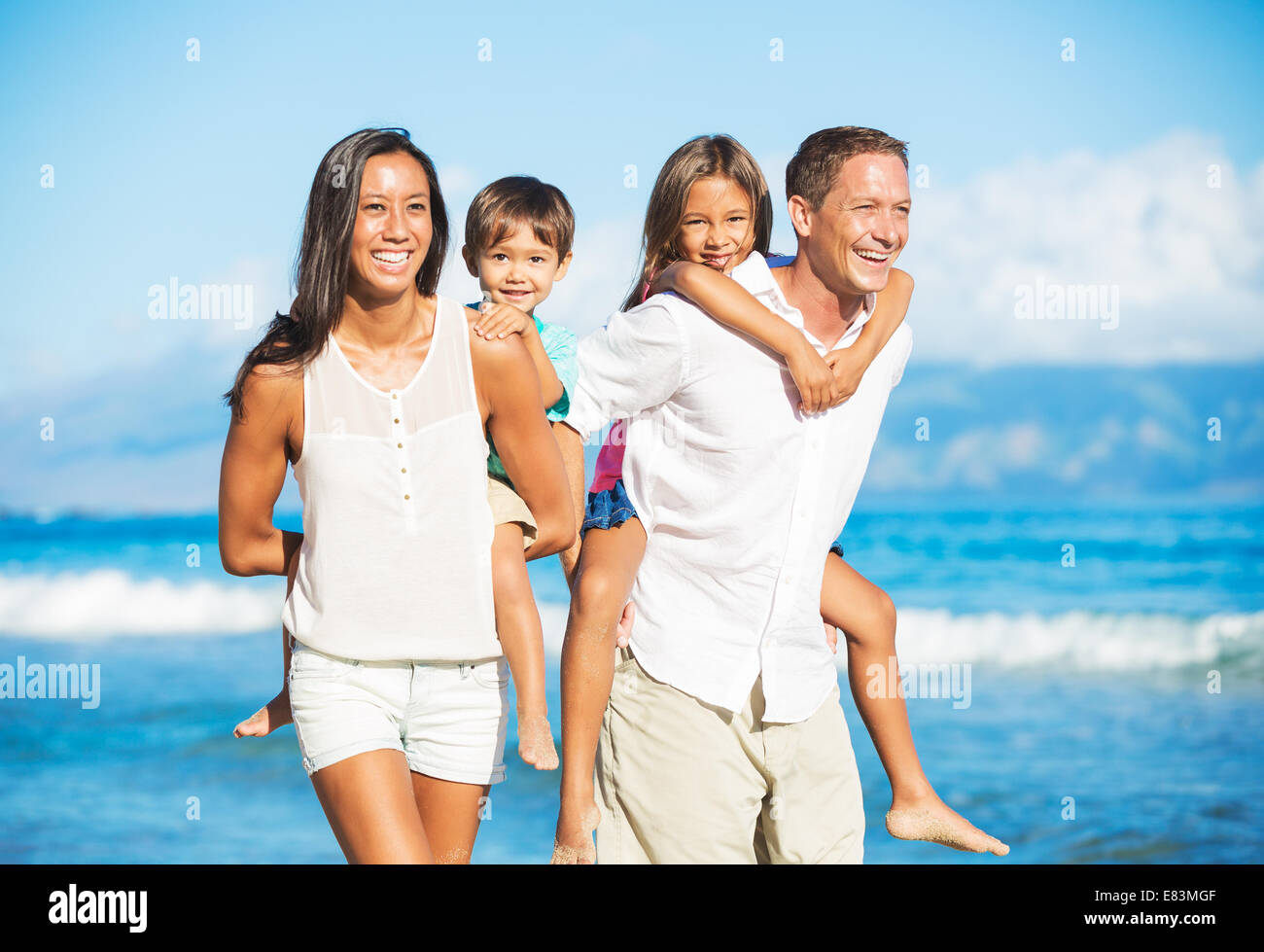 Happy Portrait of Mixed Race Family on the Beach - Stock Image