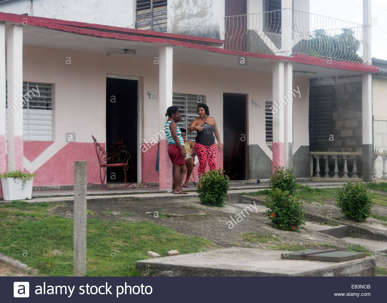 Cuban neighbors talking in front of their house during a Saturday afternoon - Stock Image